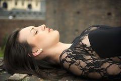 躺下在砖墙上的俏丽的深色的少妇 免版税库存图片