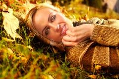 躺下在秋叶的美丽的妇女 免版税库存照片