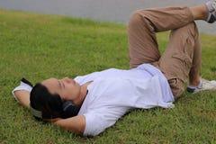 躺下在绿草的年轻亚裔人画象在自然背景中放松时间 免版税库存图片