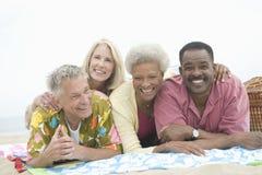躺下在胃的不同种族的朋友在海滩 库存照片