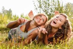 躺下在草的两个女朋友 免版税库存图片