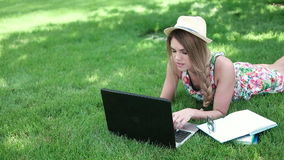 躺下在草的大学生研究膝上型计算机 股票录像