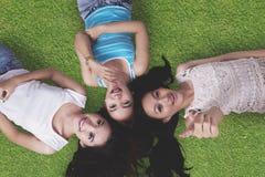 躺下在草的美丽的女孩 免版税库存图片