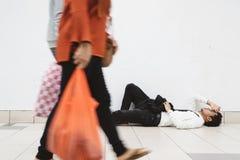 躺下在走道的年轻亚洲商人认为他的问题和看很沮丧 库存图片