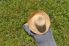 躺下在绿色领域的帽子的一个人 免版税库存照片