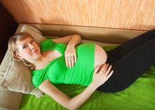 躺下的怀孕的沙发妇女 图库摄影