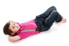躺下英俊的年轻的男孩。 免版税库存图片