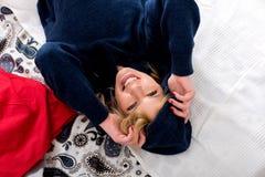躺在一件蓝色运动衫的床上的一个微笑的少妇 免版税库存图片