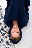 躺在一件蓝色运动衫的床上的一个微笑的少妇 图库摄影