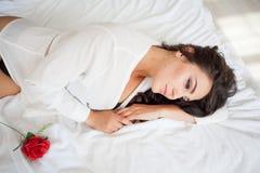 躺在与玫瑰的床上的女用贴身内衣裤的女孩 免版税库存照片
