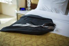躺在床上的夹克在旅馆客房 免版税库存照片