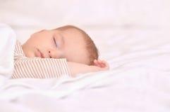 躺在床上的平安的婴孩,当睡觉在一间明亮的屋子时 免版税图库摄影