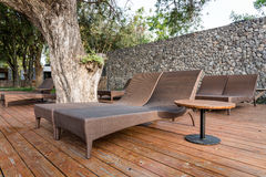 躺椅在游泳池旁边的庭院里 免版税库存照片