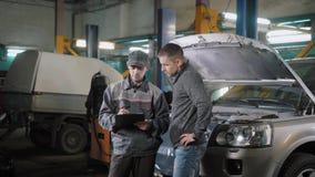 车主在汽车修理计划听着维修车间的一位汽车机修工,看,同意并且给钥匙 影视素材