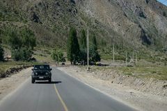 车在一条路在一个山区移动 免版税库存图片