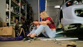 车库修理的性感的金发碧眼的女人汽车 影视素材
