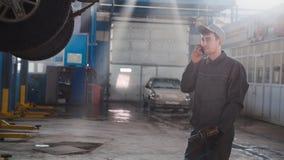 车库汽车服务-技工近被举的汽车发表演讲关于手机,广角 库存图片