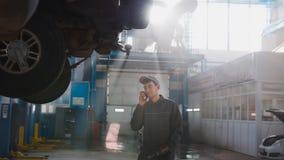车库汽车服务-技工近被举的汽车发表演讲关于手机,远距照相 图库摄影