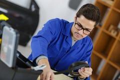 车库的人与机械零件 免版税库存照片