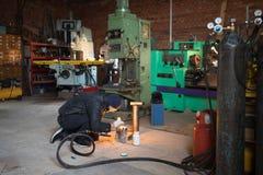 车库的人,与火焰灼烧的气焊 库存图片