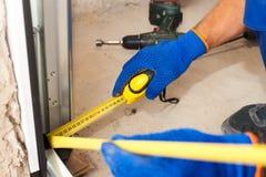 车库门设施 工作者对mesure的用途ruller距离到金属外形 免版税库存图片