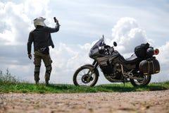 车手人拿着一个智能手机,丢失了信号,移动通信覆盖面,路冒险摩托车与旁边袋子和 库存图片