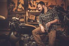 车手和他的葡萄酒样式咖啡馆竟赛者摩托车 免版税库存照片