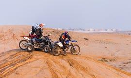 车手在种族,多灰尘的沙漠面前 免版税图库摄影