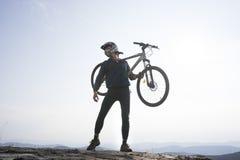 车手的剪影与自行车的 免版税图库摄影