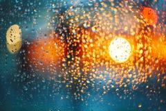 车灯通过与雨下落的玻璃 迷离bokeh 图库摄影