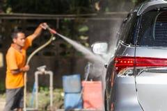 洗车的人喷洒的压力洗衣机在汽车保养商店 Focu 库存图片