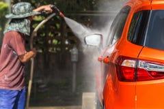 洗车的人喷洒的压力洗衣机在汽车保养商店 Focu 免版税图库摄影