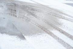 车胎踪影在雪的在路在寒冷冬天天 免版税图库摄影