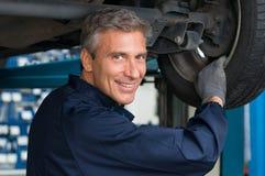 车间改变的轮胎的技工 免版税库存图片