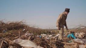 转储的男性无家可归的饥饿的人喝寻找在包裹的衣物食物与走的肮脏的生活方式是 影视素材