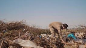 转储的肮脏的男性无家可归的饥饿的人喝寻找在包裹的食物与走去寻找慢的食物 股票录像