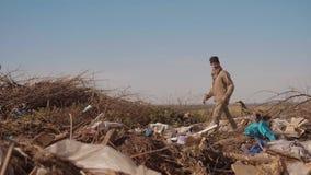 转储的肮脏的男性无家可归的饥饿的生活方式人喝寻找在包裹的衣物食物与走去 股票视频