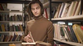 转动一本书的页的年轻人在图书馆里在书架之间 股票录像