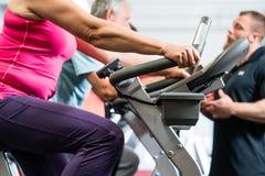 转动与个人教练员的前辈在健身房 免版税图库摄影