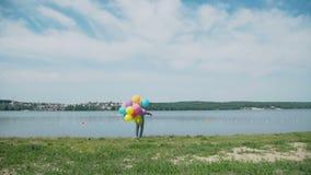 转动与在夏天海湾的五颜六色的球的愉快的女孩 股票视频