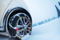 转动与在山路的防滑轮胎链子 免版税库存照片