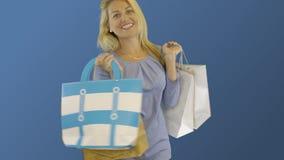 转动与购物袋的年轻白种人妇女在蓝色backgound 在购物以后的愉快的白肤金发的女孩 影视素材
