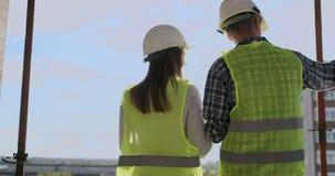 转动了建筑师和技术员在工地工作回顾的办公室图纸 股票录像