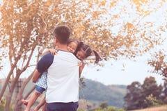 转动亚裔的父亲运载两个儿童女孩和  免版税图库摄影