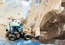 转动卸载沙子和石头工作的装载者挖掘机在constru 库存照片