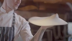 转动和扔比萨面团的两张盘年轻人在厨房里在餐馆 做比萨的专业pizzaiolo 影视素材