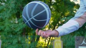 转动在一个手指,有日落的公园,树的篮球在背景,开阔地带中 股票录像