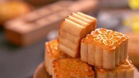 转动在一个木在黑板岩背景的盘子用茶和花的美丽的月饼 中国传统中间秋天 股票视频