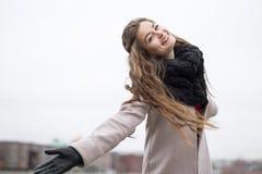 转动在一件黑外套、围巾和一件红色礼服的街道秋天码头阴云密布女孩的美丽的女孩反对灰色天空 没有 图库摄影