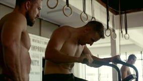 转动在健身房的固定式自行车的肌肉人与教练 股票录像